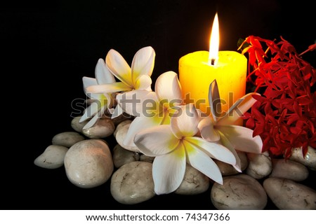Flowers with candle white rock for spa use isolated on black.