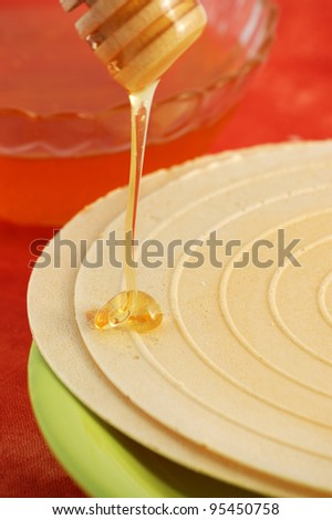 Flowing honey and waffle on red background