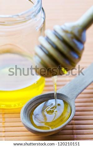 flowing honey in wood spoon