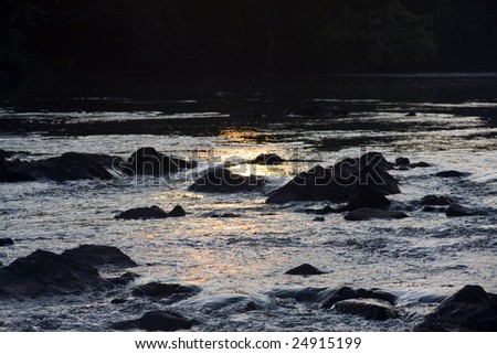 flowing river just at the end of sunset - stock photo