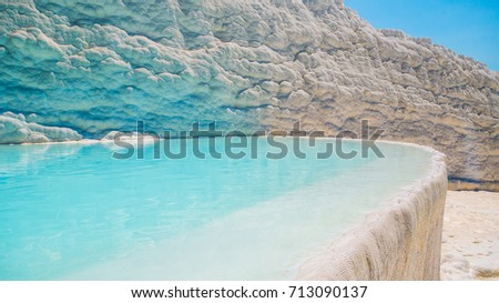 Flowing slowly down the huge mountainside, mineral water collect in terraces, dripping over balconies of stalactites into milky pools.  Pamukkale, Turkey. #713090137