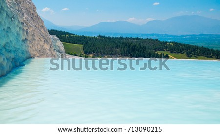 Flowing slowly down the huge mountainside, mineral water collect in terraces, dripping over balconies of stalactites into milky pools.  Pamukkale, Turkey. #713090215