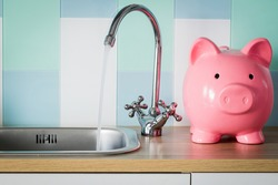 Flowing tap water and a piggy bank standing next to it. Water consumption price concept