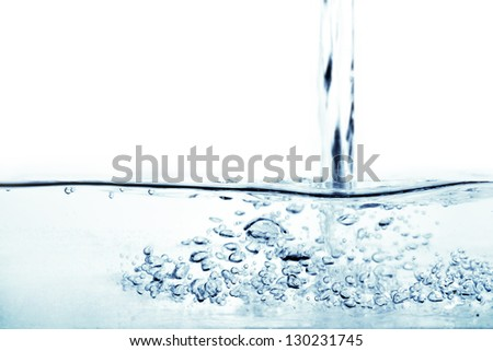 Flowing water and air bubbles over white background