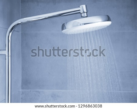 Flowing water from modern shower head at bathroom interior, nobody. Blue tone