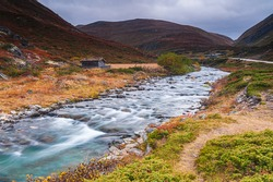 Flowing water in autumn colored mountain landscape