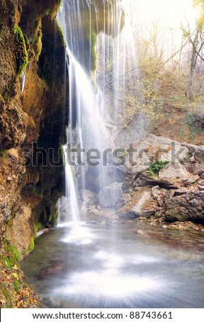 flowing waterfall on a cliff in the autumn season