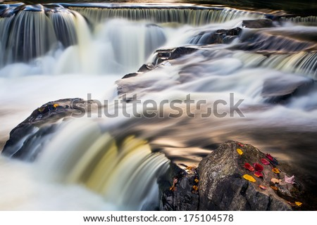 Flowing whitewater cascades over rock ledges at Bond Falls, a waterfall in Michigan's Upper Peninsula.