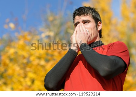 Flu and cold man. Young athlete coughing and blowing on a tissue. Caucasian hispanic male model.