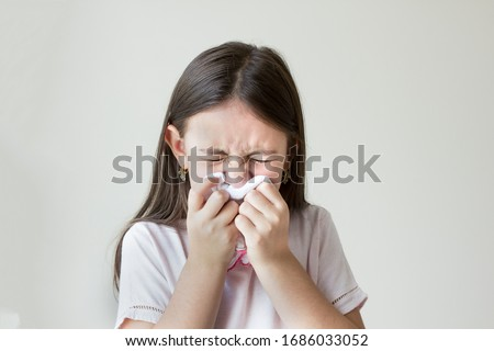 Flu concept - Upset and sick child blowing his nose with flu symptoms coughing at home, Allergic girl, flu season. Girl with cold rhinitis, cold Stock photo ©