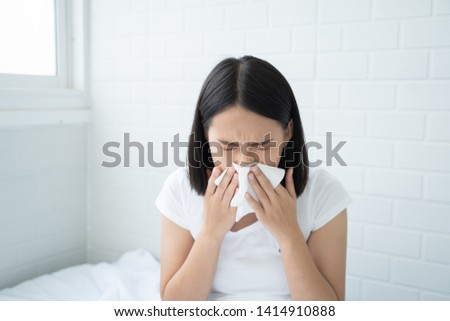 Flu.Rhinitis, cold, sickness, allergy concept. Young Asian woman got nose allergy, flu sneezing nose sitting at bed in bedroom,female. Brunette sneezing in a tissue