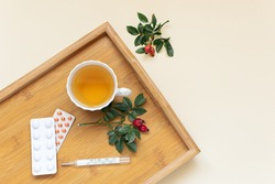 Flu season concept. Cup of herbal tea, tablets in blisters and thermometer on the wooden tray top view, copy space for your design.