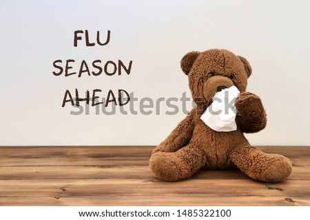 "Flu: teddy bear with a tissue because of a runny nose with the words ""flu season ahead"" in the background #1485322100"