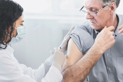 Flu Vaccine. Close up of young latina nurse giving elderly male patient injection in hospital room, copyspace