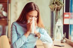 Flu. Young woman got nose allergy, flu sneezing nose sitting at the table in a trendy cafe coffee shop with a cup of hot beverage beside