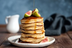 Fluffy buttermilk pancakes with figs and syrup pouring over. Delicious appetizing stack of thick pancakes