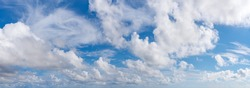 Fluffy cumulus clouds, translucent cirrus and stratus clouds float slowly across the bright blue sky on a sunny day. Panoramic skyscape shot. Weather, meteorology and types of clouds. Beauty in nature