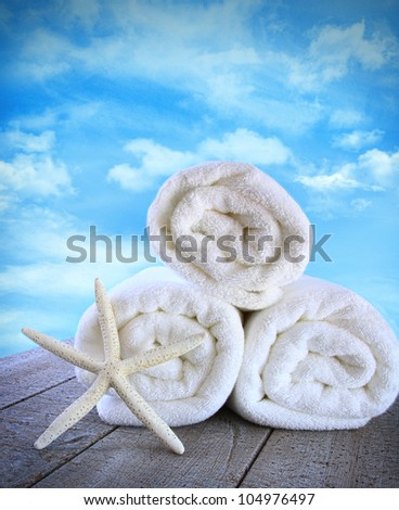 Fluffy fresh towels against a blue sky with clouds - stock photo