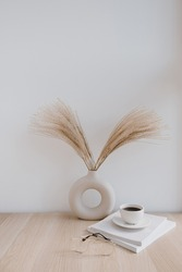 Fluffy pampas grass / reed in stylish vase, coffee cup, glasses and magazines against white wall. Minimal interior decoration. Styled concept for bloggers. Parisian vibes.