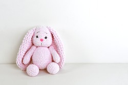 Fluffy pink bunny toy with long ears sitting near a white wall. Copy space.