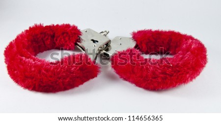 Fluffy red handcuffs isolated on white