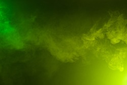 Fluffy smoke on dark background colored with yellow and green lighting.
