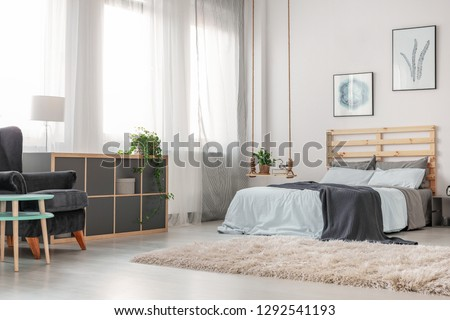 Fluffy white carpet on the floor of trendy bedroom with king size bed with wooden headboard, posters on the wall and fashionable swing as nightstand #1292541193