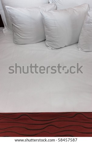 Fluffy white pillows against a white sheet with a red blanket.