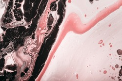 Fluid Art. Abstraction from black paint bubbles and pink coral waves. Marble effect background or texture.