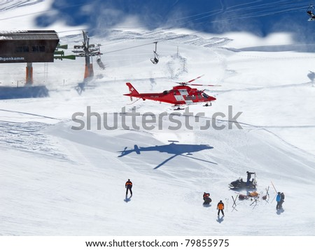 FLUMSERBERG, SWITZERLAND - MARCH 5: A rescue helicopter evacuas a skier after an accident in Flumserberg, Switzerland on March 5, 2011. Skiing safety becoming an issue on crowded slopes. - stock photo