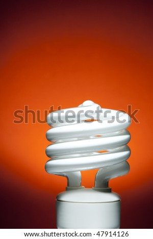 Fluorescent Bulb on Red Orange Background.  Studio lit with spot lit background.