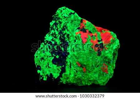 fluorescent minerals calcite (red), willemite (green) and franklinite (black) in shot wave ultraviolet light