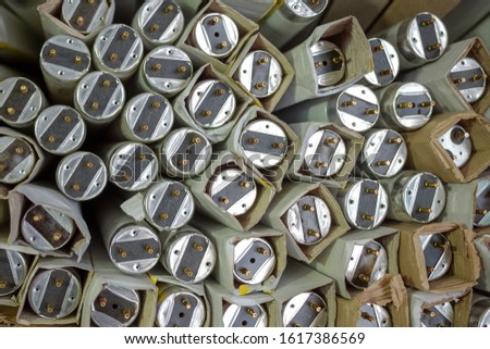 Fluorescent tube light. Many old spoiled, glass fluorescent lamps are in paper packaging for recycling. Harmful to environment. Abstract background. Close-up.