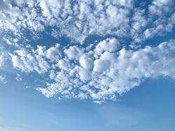 Flushed, fluffy white clouds scatter in full light blue sky.