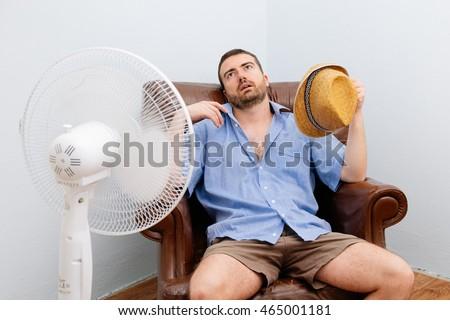 Flushed man feeling hot in front of a fan  #465001181