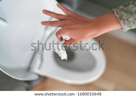 Flushing down disinfectant wipes as toilet paper shortage alternative during panic buying coronavirus outbreark causing home toilets to clog. Foto stock ©