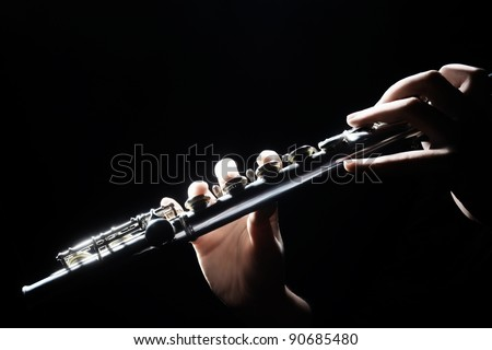 Flute music instrument details playing. Hand of flutist musician on black