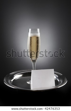 Flute of Champagne shot on silver tray with white place card including space for copy