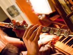 flute played by the skillful and fast fingers of a musician with a piano keyboard in the background