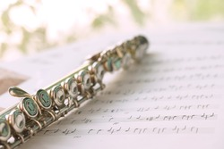 Flute, woodwind brass instrument in classical orchestra. Silver modern flute on white sheet music note for education and performance. Song composer on papers sway by wind.