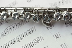 Flute, woodwind brass instrument in classical orchestra. Silver modern flute on white sheet music note for education and performance. Song composer on score sheet for orchestra.
