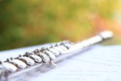 Flute, woodwind brass instrument in classical orchestra. Silver modern flute on white sheet music note for education and performance. Song composer on score sheet with green bokeh nature.