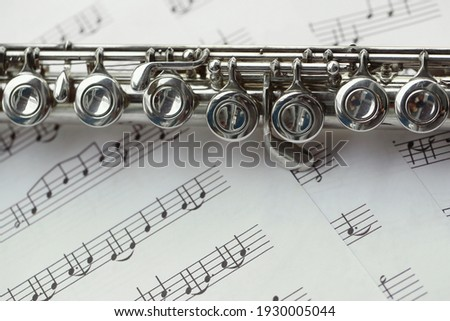 Flute, woodwind brass instrument in classical orchestra. Silver modern flute on white sheet music note for education and performance. Song composer on score sheet for orchestra. Foto d'archivio ©