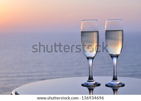 Flutes of champagne with sunset background