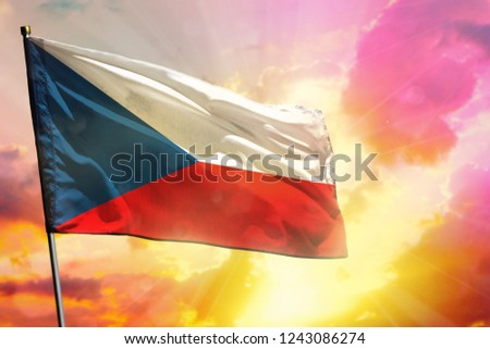 Fluttering Czechia flag on beautiful colorful sunset or sunrise background. Czechia success and happiness concept.