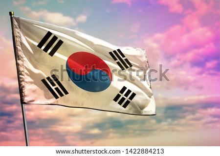 Fluttering Republic of Korea (South Korea) flag on colorful cloudy sky background. Republic of Korea (South Korea) prospering concept.