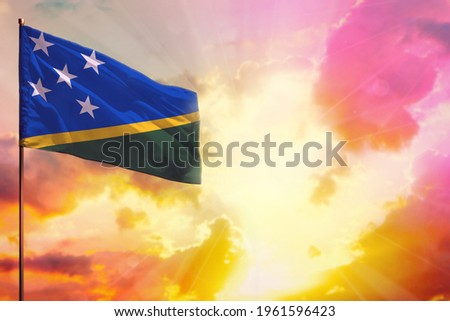 Fluttering Solomon Islands flag in left top corner mockup with the place for your information on beautiful colorful sunset or sunrise background. Foto stock ©