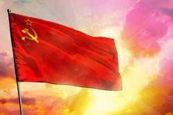 Fluttering Soviet Union (SSSR, USSR) flag on beautiful colorful sunset or sunrise background. Soviet Union (SSSR, USSR) success and happiness concept.