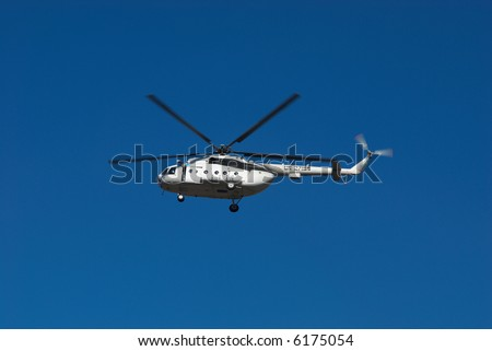 Fly big white helicopter on blue sky