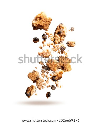 Fly crumbs of oatmeal cookies. Cookie crumbs with chocolate pieces isolated on white background. Crumbs of oatmeal cookies closeup.